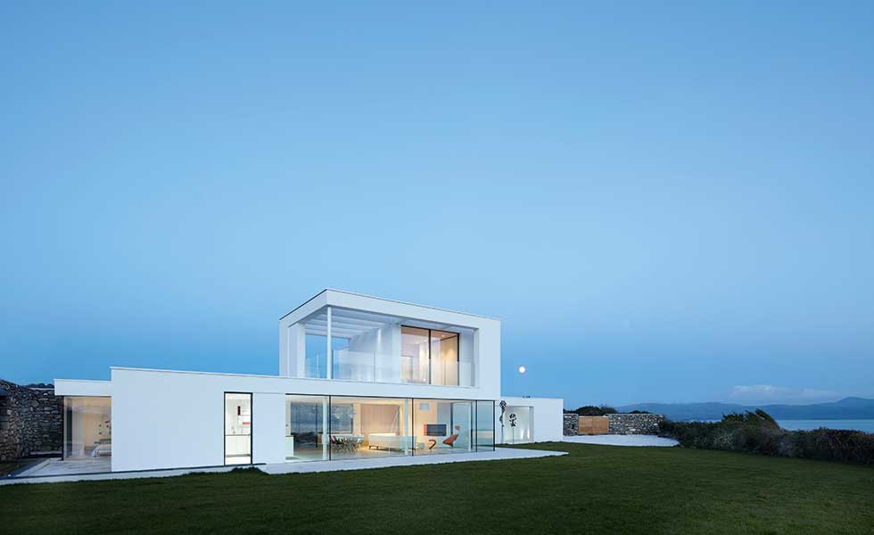 A white rendered project in Wales by Stephenson Studio overlooks sea and mountain views