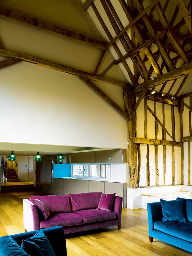 Varied ceiling heights and vaulted ceiling in a barn conversion with brightly covered velvet furniture
