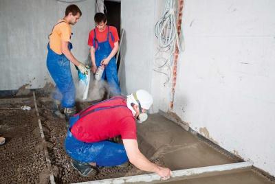 three workmen pouring a concrete floor