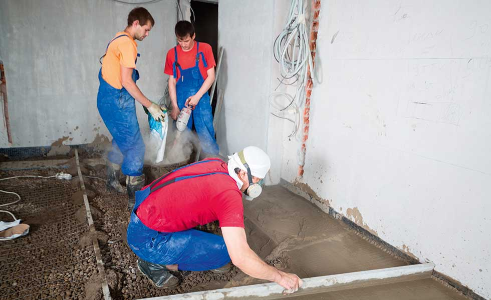 three workmen pouring a concrete floor