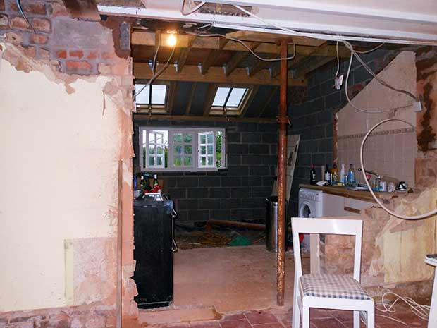 The kitchen extension with exposed wires and pipes