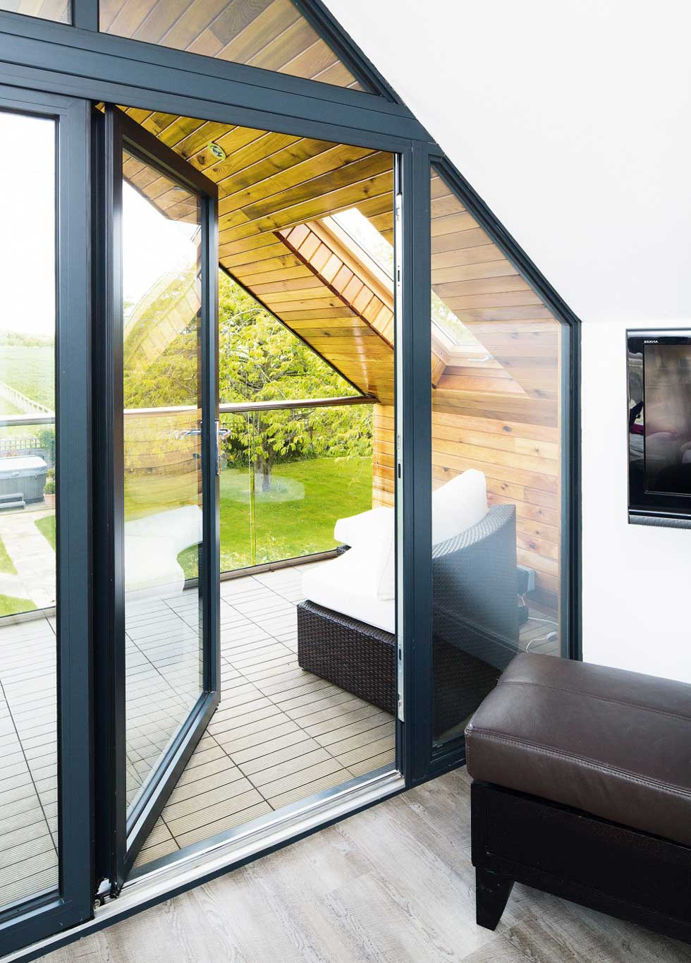 A glass door leads out onto the decked terrace