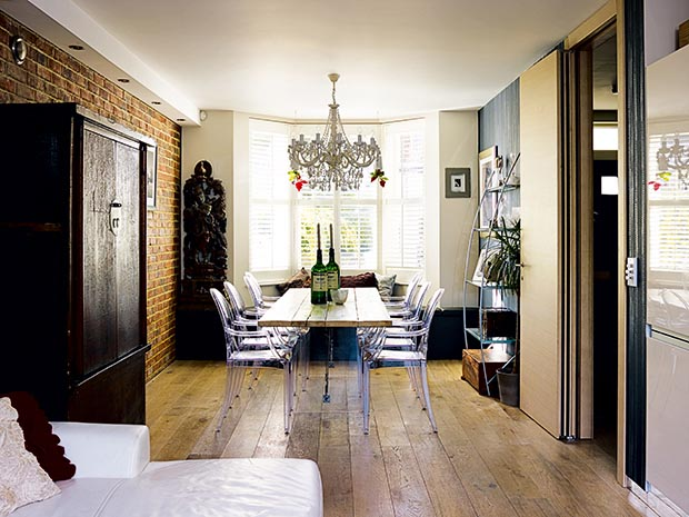 Ground floor dining room and open plan kitchen with exposed brick and chandelier