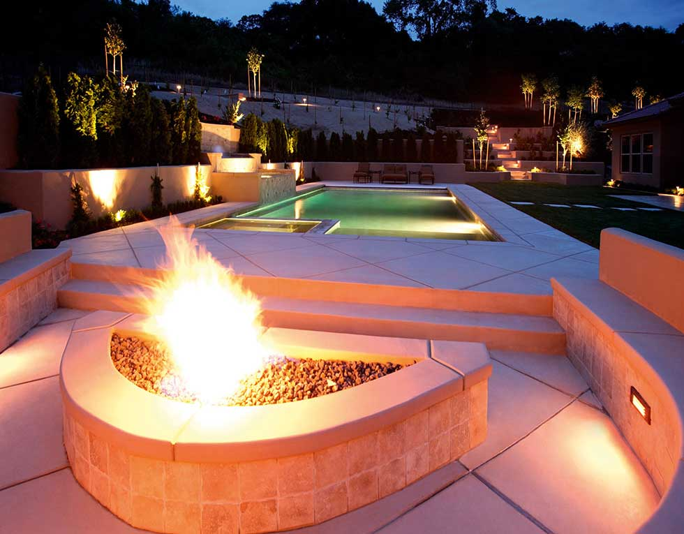 fire pit and pool at night in a luxury garden
