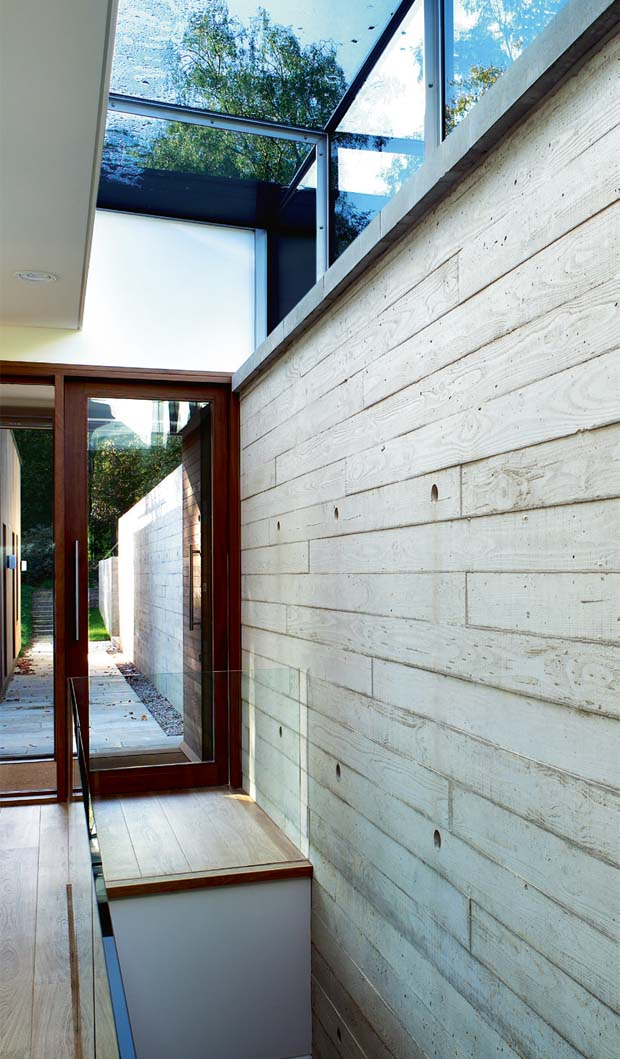 A concrete wall runs from the outside into the house