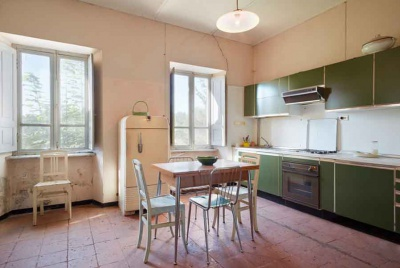 kitchen with green cabinets and cracked walls