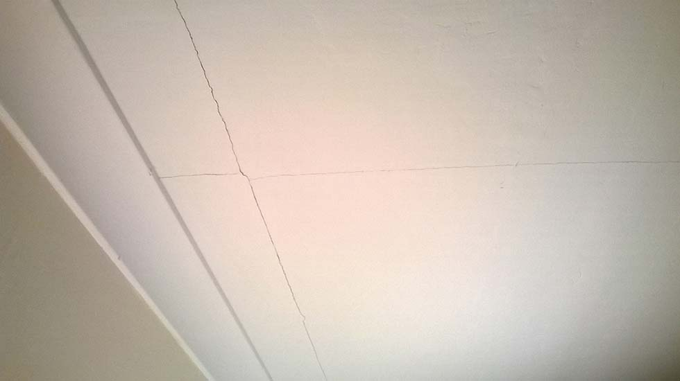 Cracks in a plasterboard ceiling painted white
