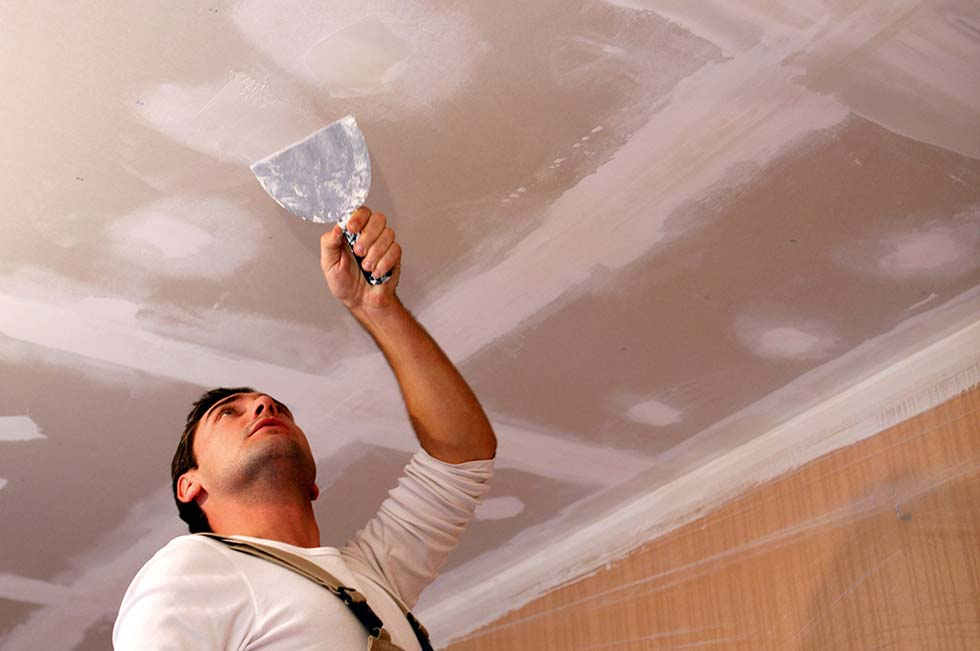 Repairing cracks and dents in a ceiling with skim