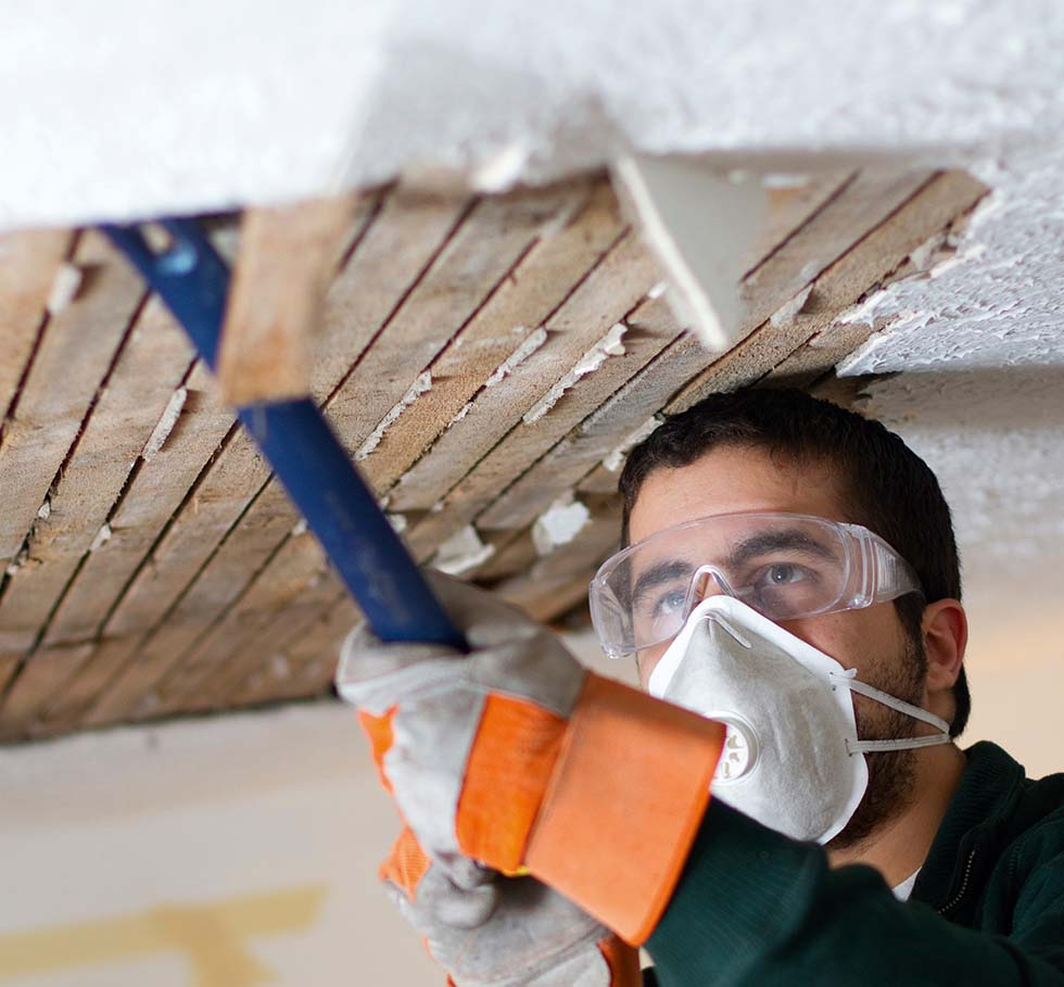 Man wearing a face mask bringing down a sagging lath and plaster ceiling