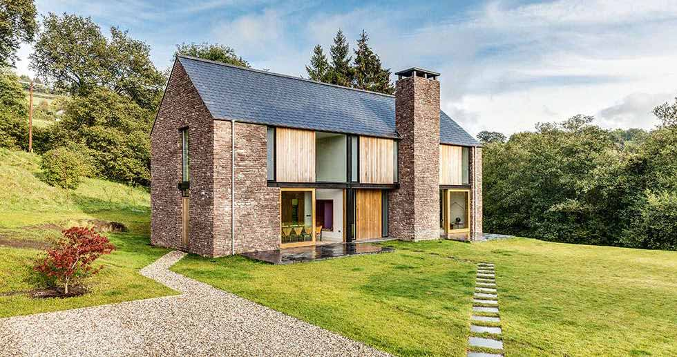 A steel frame barn-style house clad in stone and timber