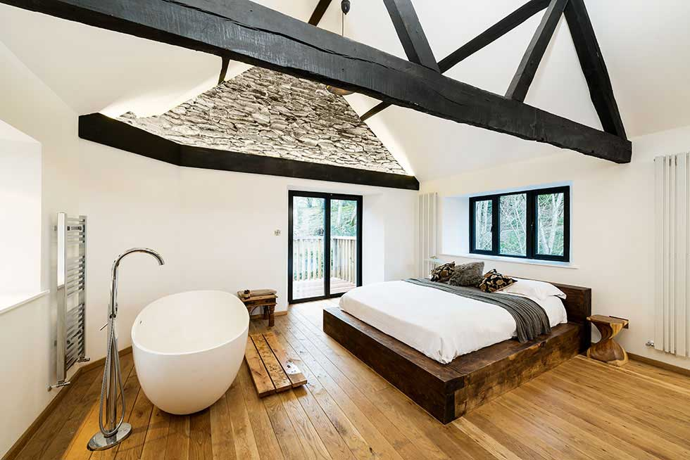 an egg bath in a bedroom with timber beams