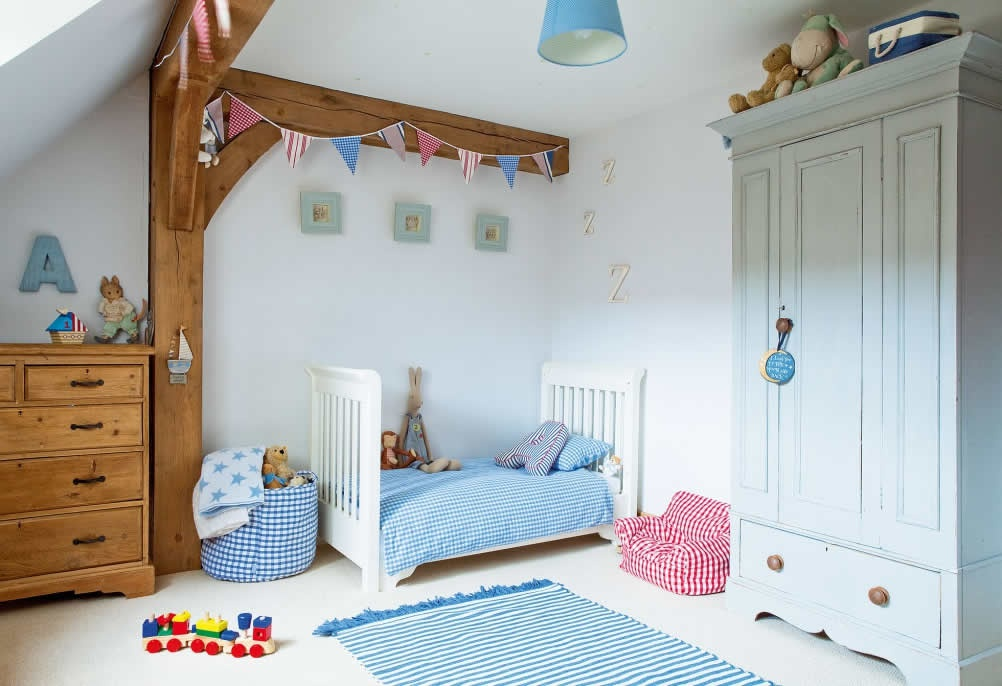 infant bedroom in a timber frame home with blue and pink furnishings