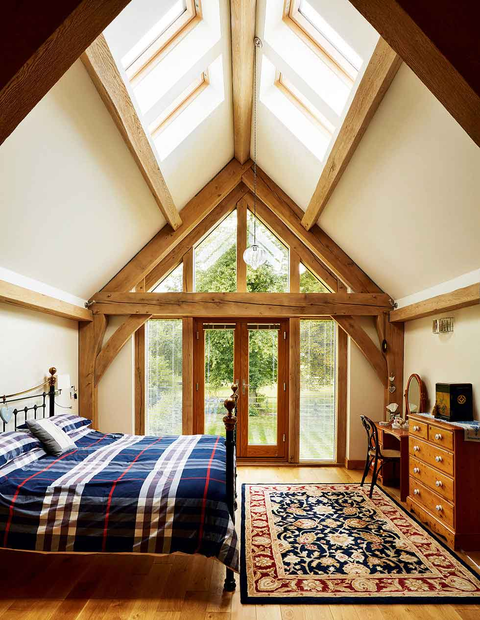 Rooflights in the vaulted ceiling and a glazed gable end ensure this bedroom gets lots of natural light