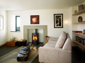 A woodburning stove acts as a focal point and adds warmth to a smaller snug