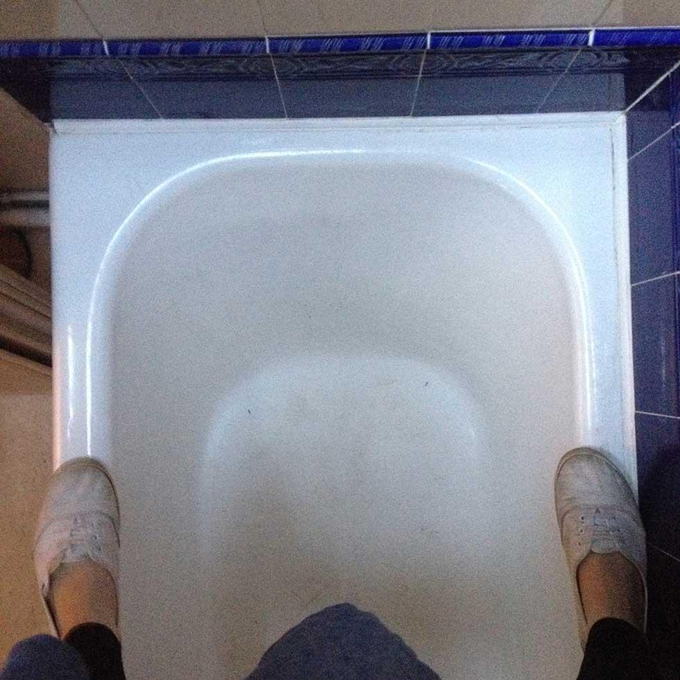 Lindsey standing on enamelled bath to look in loft