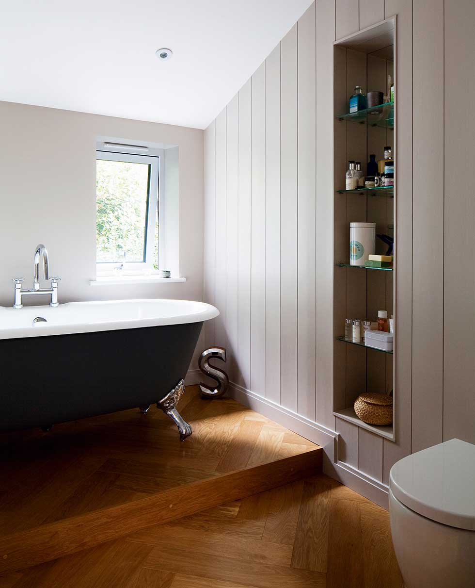 The bathroom has a raised platform for the freestanding bath and herringbone flooring
