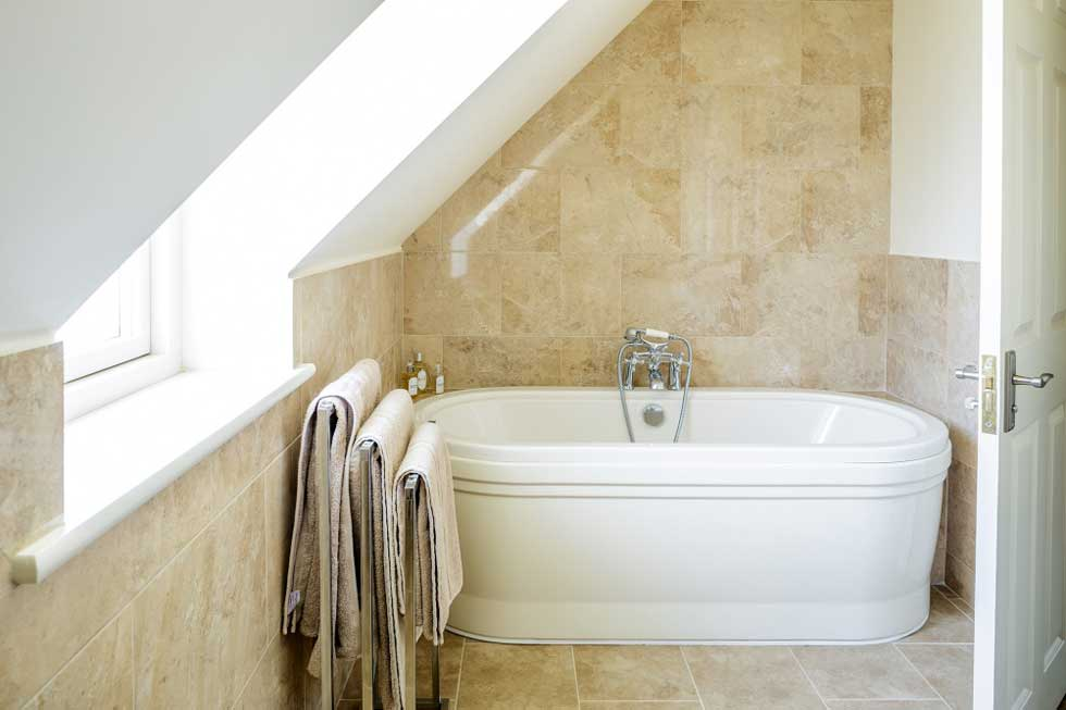 The family bathroom with neutral floor and wall tiles