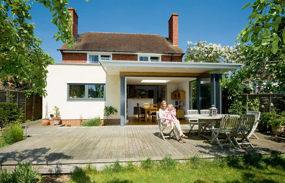 mother and daughter sitting in front of single storey extension bifold doors open
