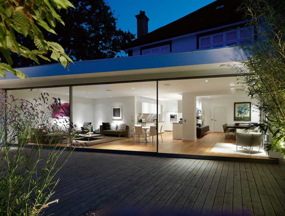 large glass sliding doors on single storey extension at night