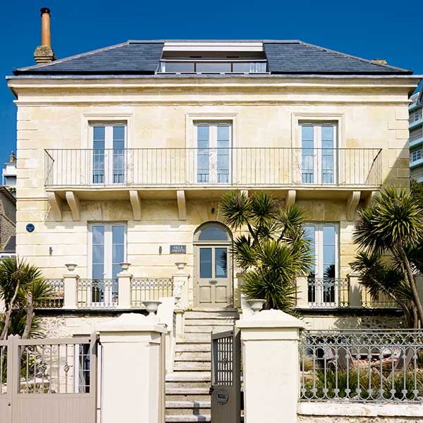 This seafront Georgian villa with banded cut stone façade has been expertly restored