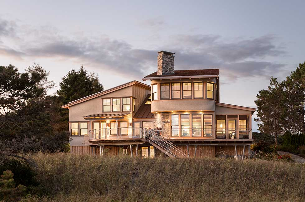 Exterior image from the sand of CJAB's beach house project at dusk in Maine