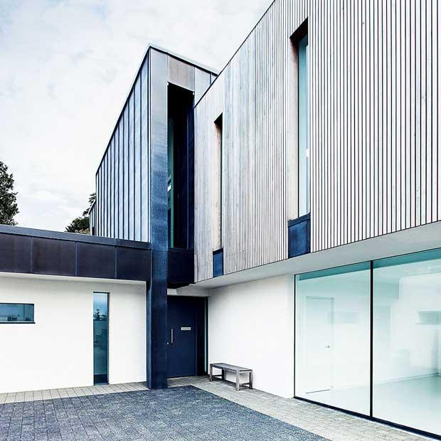 Low-maintenance exterior finish of render, zinc and cedar