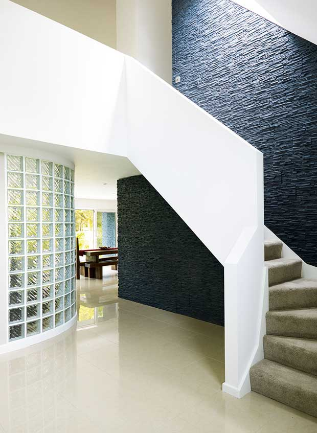 Curved glass wall seperates the living area from the entrance hall