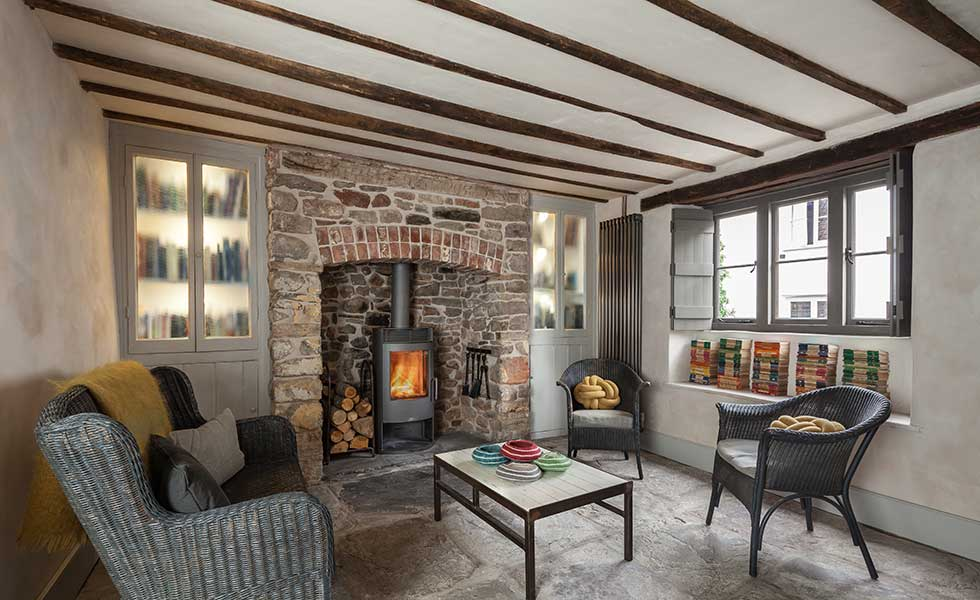 living room in a cottage with exposed stone hearth and woodburning stove