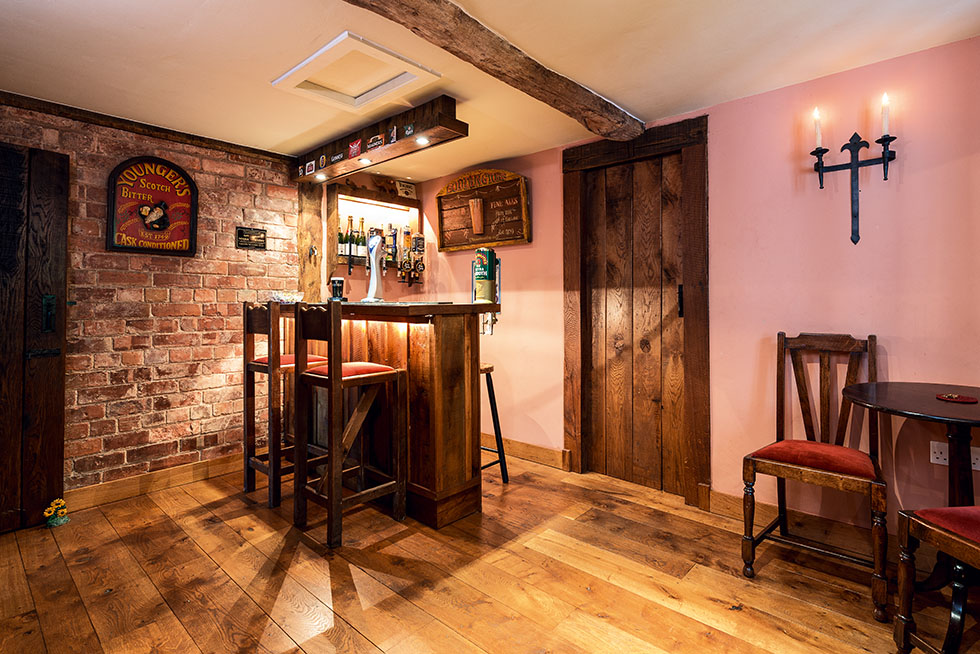 Located off the main dining room, this home bar offers a cosy country pub feel with exposed brickwork, and traditional, handcrafted wooden details. View Project →