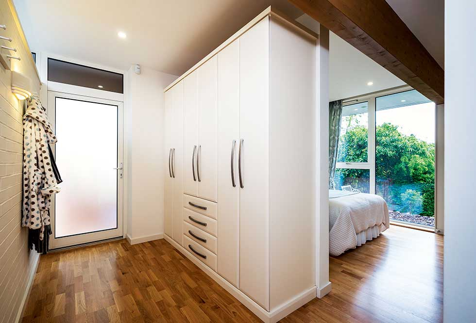 Built-in wardrobes create a partition wall between bedroom and dressing room