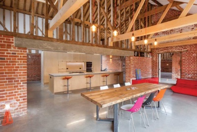 This barn conversion with its wide openings and lofty ceiling heights is perfect for entertaining. A large dining table runs parallel to the kitchen island