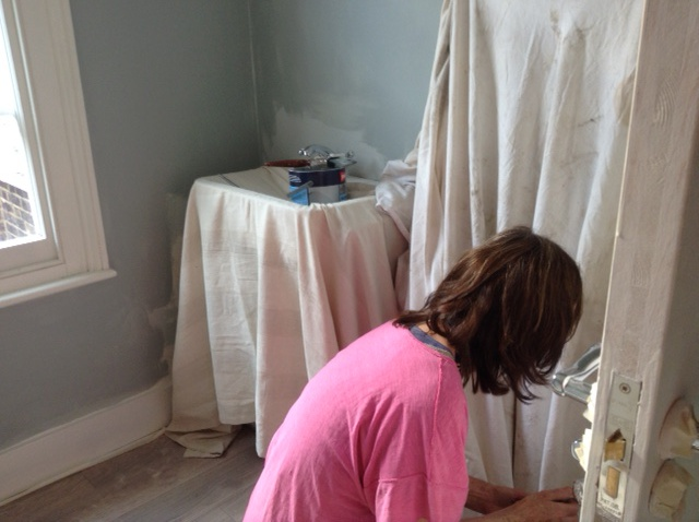lady in pink tshirt painting a bathroom