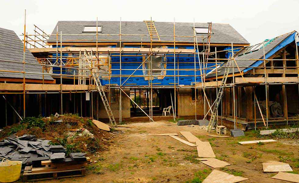 slated roof and hempcrete oak frame house surrounded by scaffold
