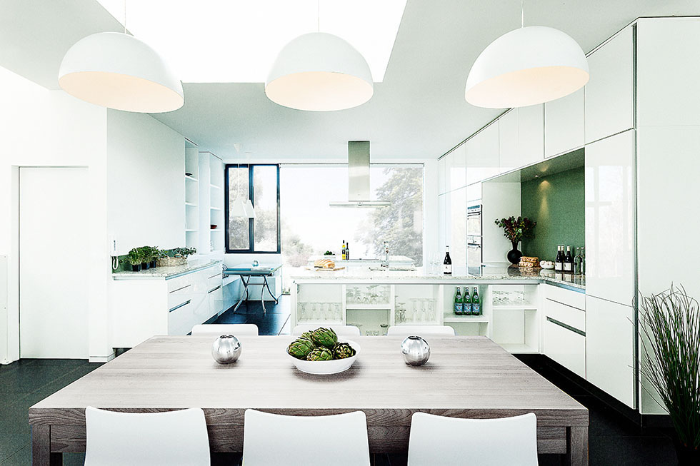 White fittings and furniture enhance the sense of light and space in this kitchen. View Project →