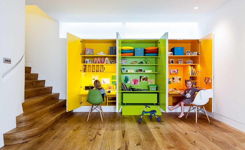 colourful basement with storage and working stations for kids