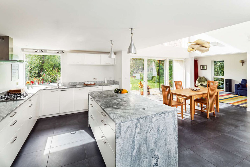 German kitchen cabinets have been teamed with granite worktops, which were honed for a matt finish. The double height dining area is ideal for entertaining. View Project →