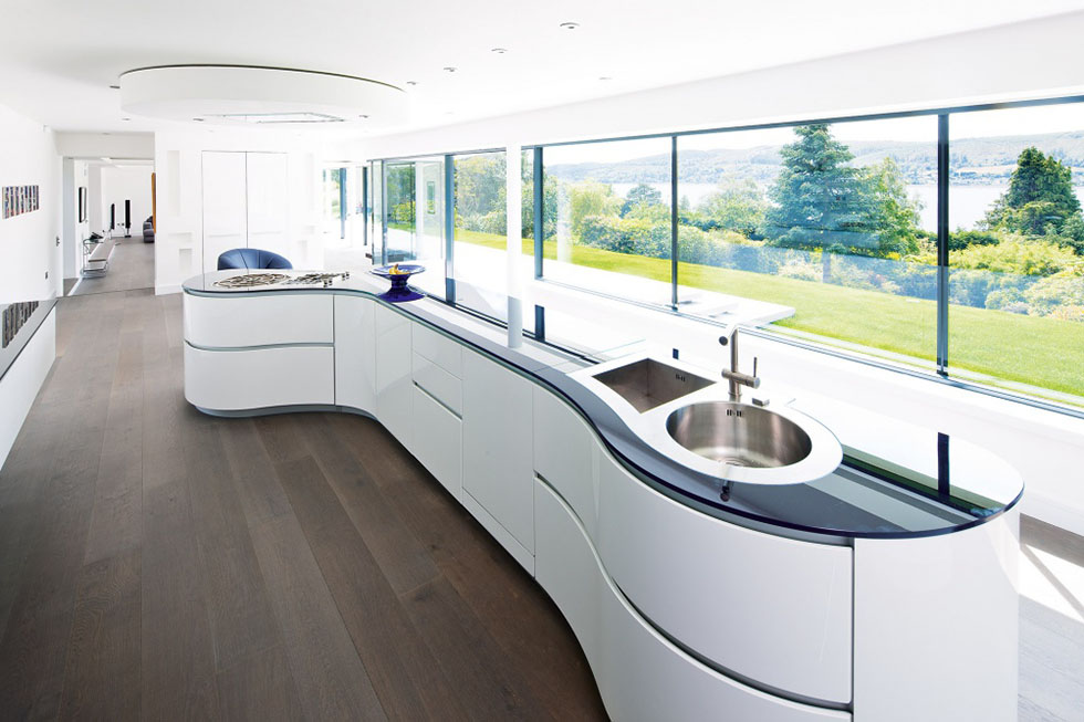The high-spec Italian curvilinear kitchen island, with integrated appliances has been angled to face the glazed wall and dramatic views beyond. View Project →