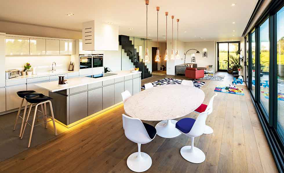 This contemporary kitchen in this open plan self build in the Greenbelt is zoned by lighting and furniture