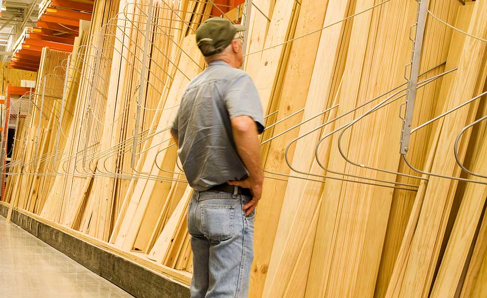 man looking at planks of wood in a builders merchants