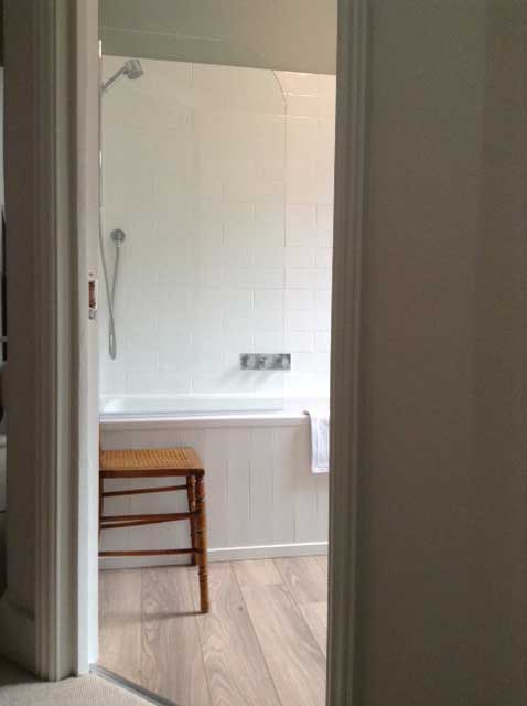 bathroom with over bath shower and glass screen
