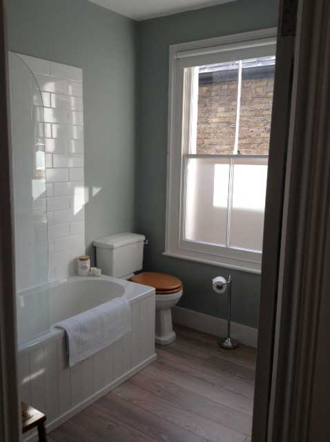 blue-green bathroom with sash window and metro tiles