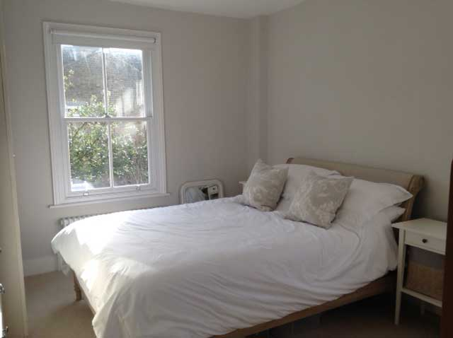 master bedroom with sash windows and white decor