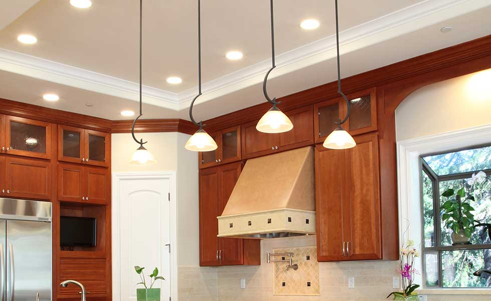 pendant lights and spot lights on the ceiling of a kitchen