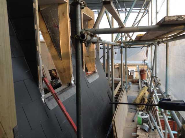 slated tile mansard roof under scaffold