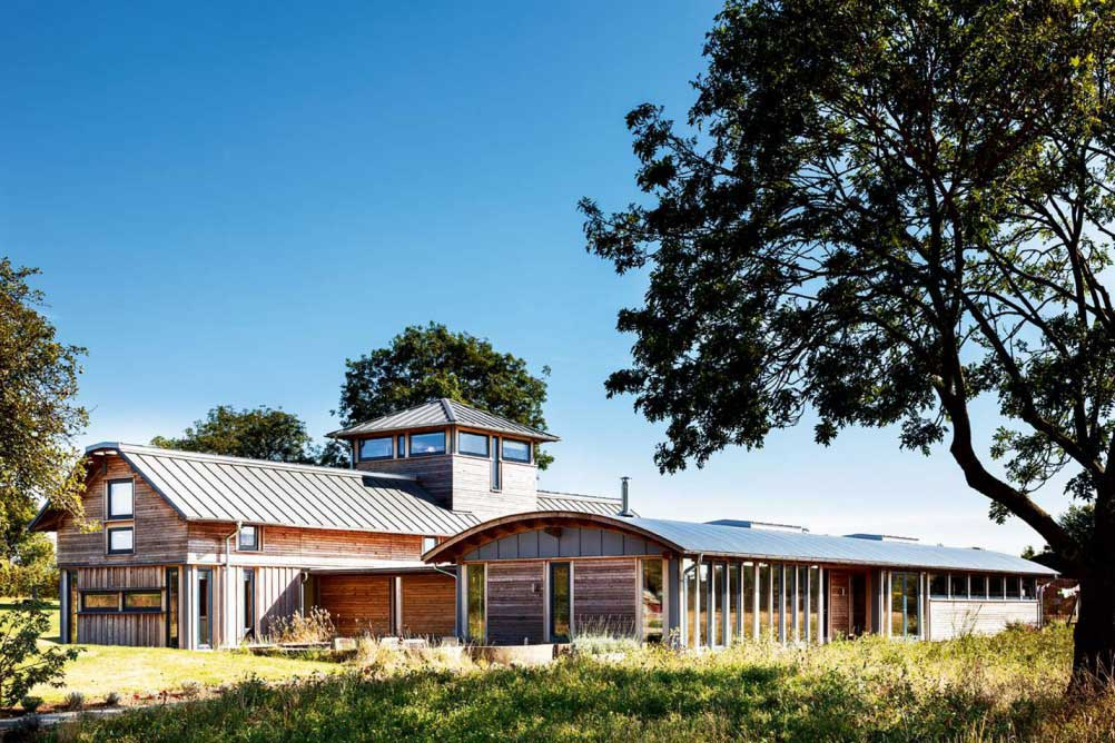 timber frame farmhouse with curved roof addition