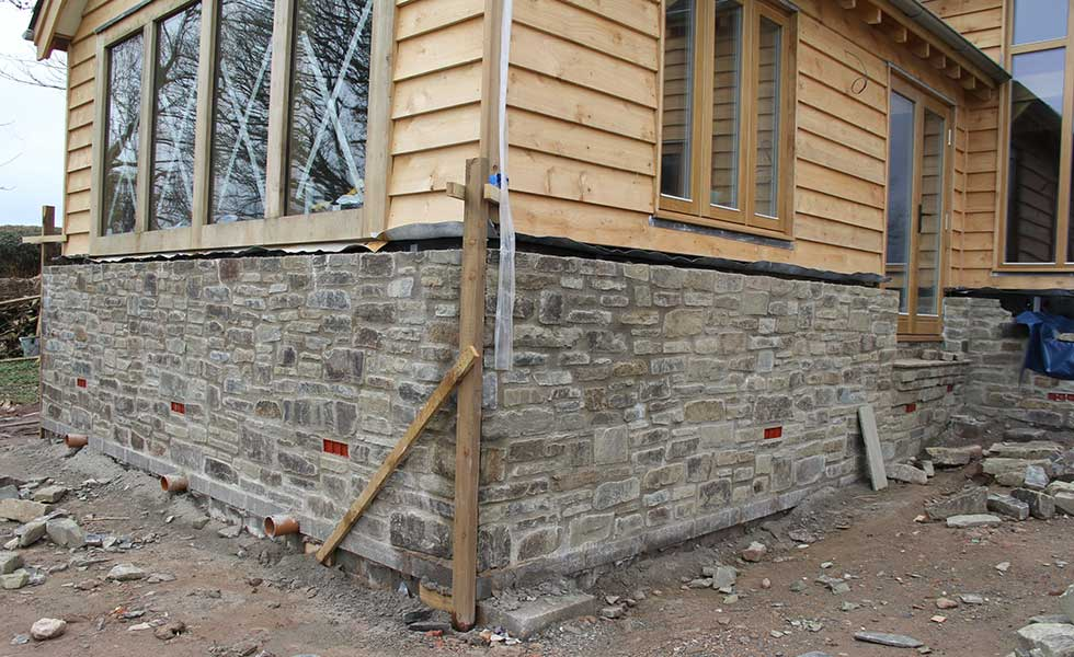 building a stonework wall on a timber clad timber frame house