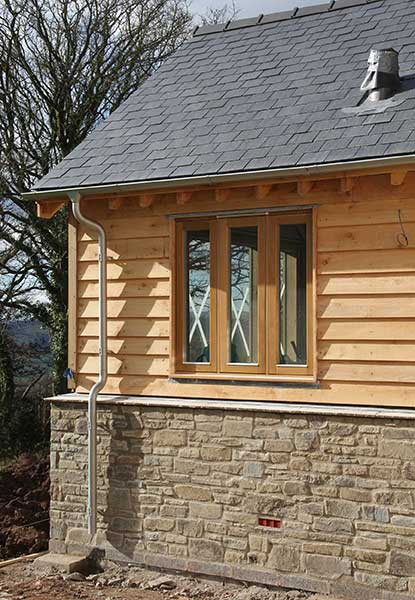 timber clad self build with stonework plinth