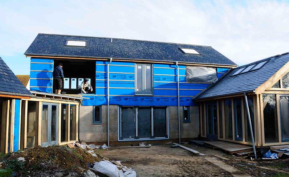 team installing windows on an oak frame home