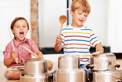 children hitting pots and pans with wooden spoons