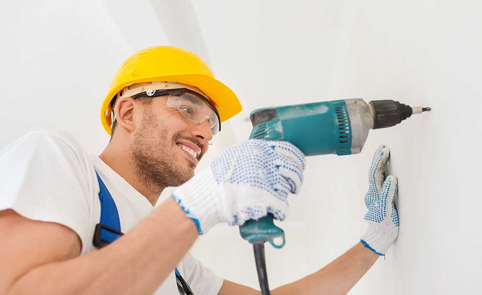 a builder in safety hard hat and goggles drilling a wall